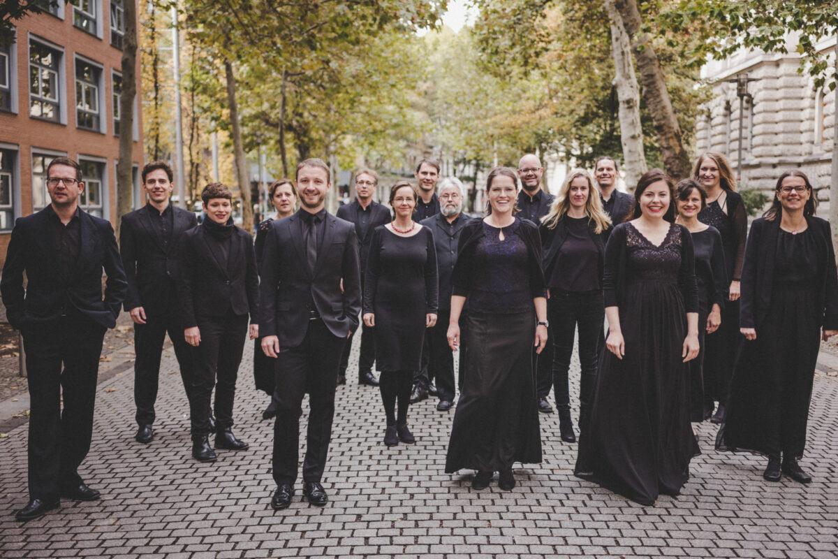 Chorsängerinnen und Chorsänger in schwarzer Kleidung laufen eine Straße entlang